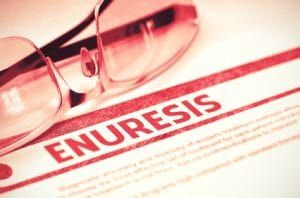 Diagnosis - Enuresis. Medicine Concept on Red Background with Blurred Text and Glasses. Selective Focus. 3D Rendering.